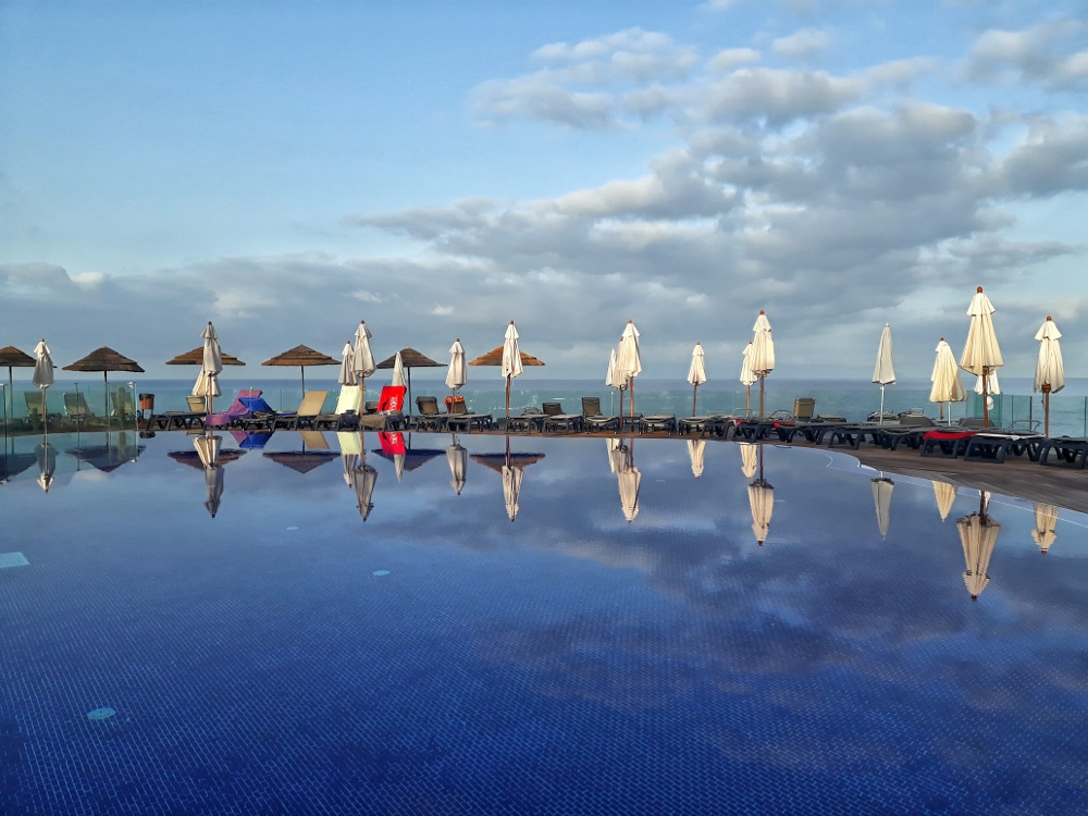 view of infinity pool lined with sunbeds